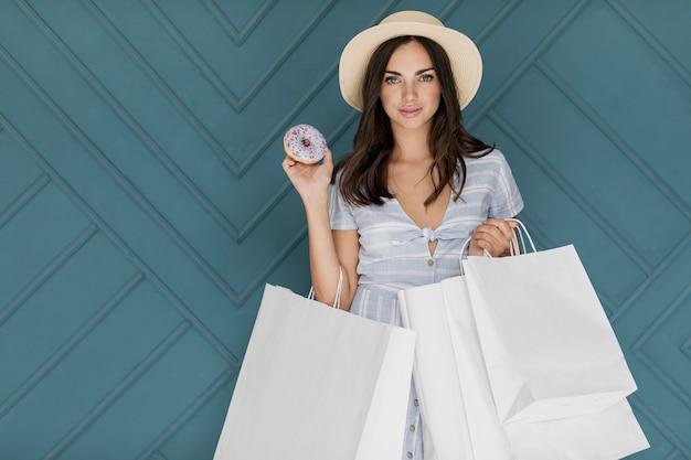 Brunettemädchen mit einem donut und vielen einkaufsnetzen