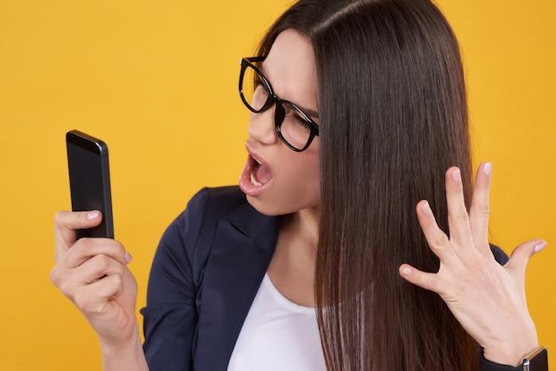 Brunettemädchenhaltungen verärgert am lokalisierten telefon.