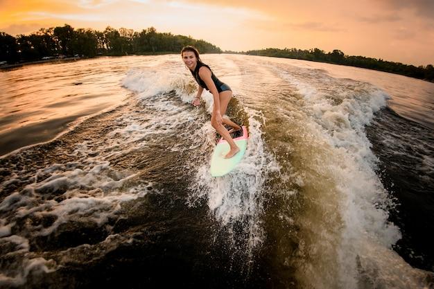 Brunettemädchenreiten auf dem wakeboard auf dem fluss auf der welle des motorboots