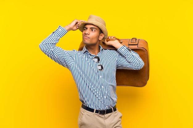 Brunettemann, der einen weinleseaktenkoffer über der lokalisierten gelben wand hat zweifel und mit verwirren gesichtsausdruck hält