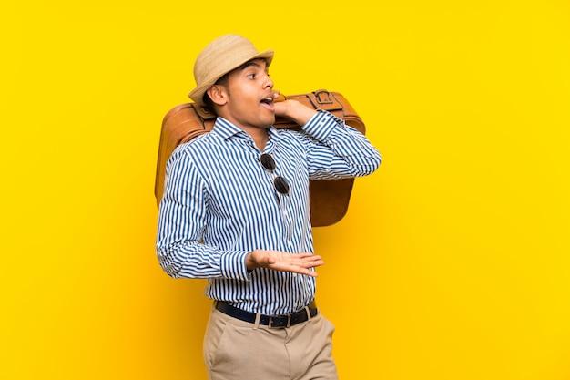 Brunettemann, der einen weinleseaktenkoffer über gelber wand mit überraschungsgesichtsausdruck hält