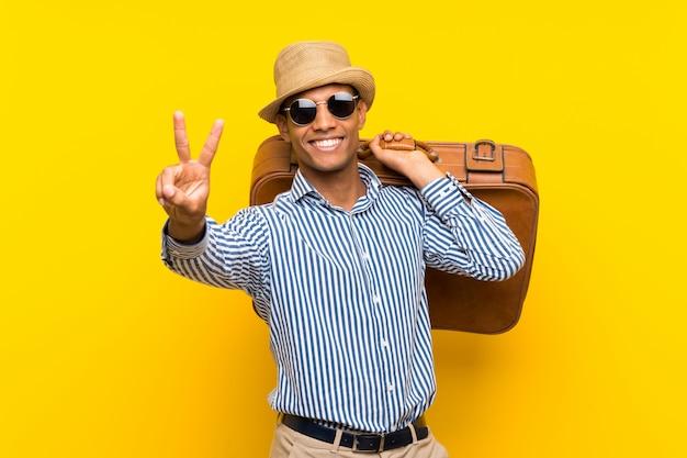 Brunettemann, der einen weinleseaktenkoffer über lokalisierter gelber wand lächelt und zeigt siegeszeichen hält