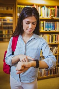 Brunettestudent, der ihre intelligente uhr in der bibliothek verwendet