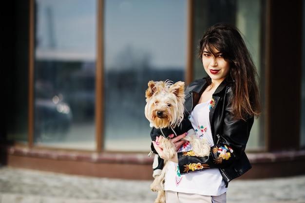 Brunettezigeunermädchen mit yorkshire-terrierhund warf gegen großes fensterhaus auf. modellabnutzung auf lederjacke mit ornament, hose.