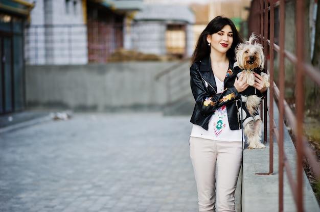 Brunettezigeunermädchen mit yorkshire-terrierhund warf gegen stahlgeländer auf. modellabnutzung auf lederjacke mit ornament, hose.