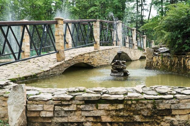 Brunnen und brücke aus steinfliesen im park. ein dekorativer teich im freien