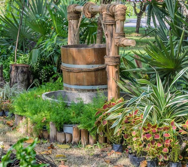 Brunnen und hölzerner eimer im garten