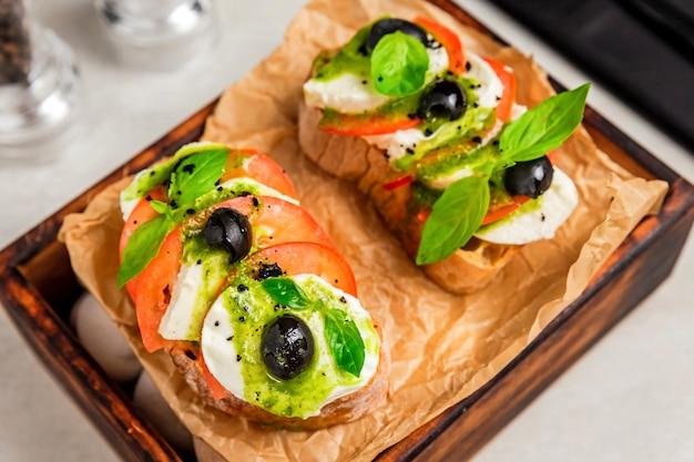 Bruschetta caprese nahaufnahmefoto, tomate, mozzarella, basilikum, schwarze olive