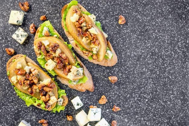 Bruschetta mit birne, honig, walnuss, käse, grünem salat und olivenöl