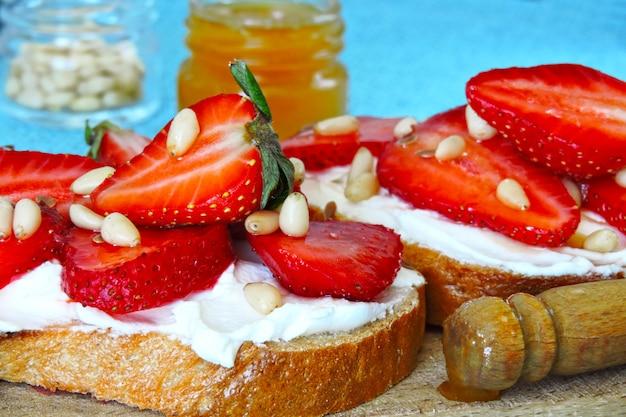 Bruschetta mit erdbeeren, frischkäse, honig und pinienkernen.