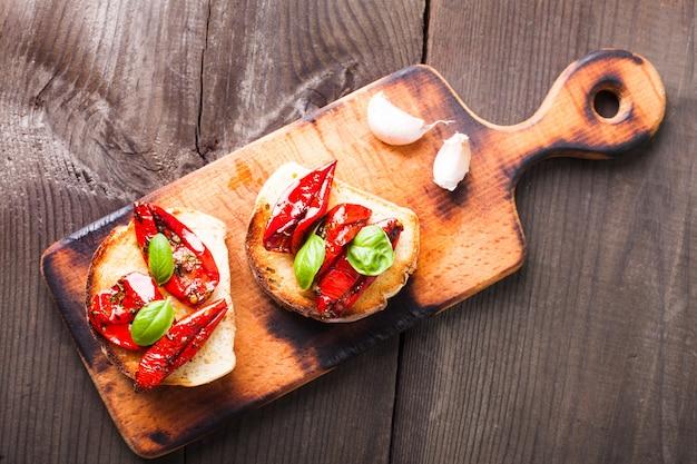 Bruschetta mit getrockneten tomaten, basilikumblättern und knoblauch