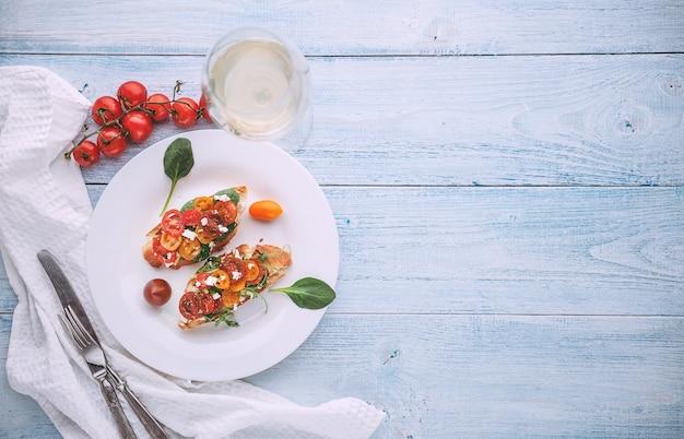 Bruschetta mit käse, basilikum, rucola und kirschtomaten und einem glas weißwein