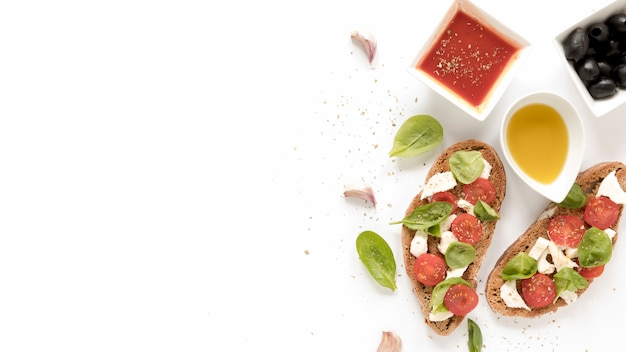Bruschetta mit käse; tomate; basilikumblätter, die nahe soße übersteigen; oliven; öl und knoblauchzehe über weiße fläche