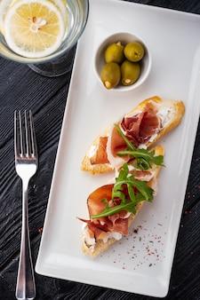 Bruschetta mit parma und ziegenkäse, oliven und mandeln. weinset