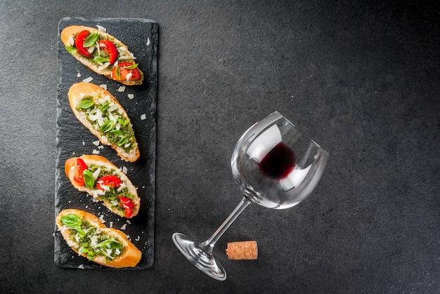 Bruschetta mit pesto, parmesan, tomaten und basilikum auf tablett mit wein