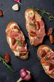 Bruschetta mit prosciutto hartkäse tomaten kräutern und gewürzen auf einem holzbrett