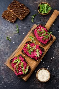 Bruschetta mit rote-bete-hummus, rucola und sesam auf dunkler betonoberfläche