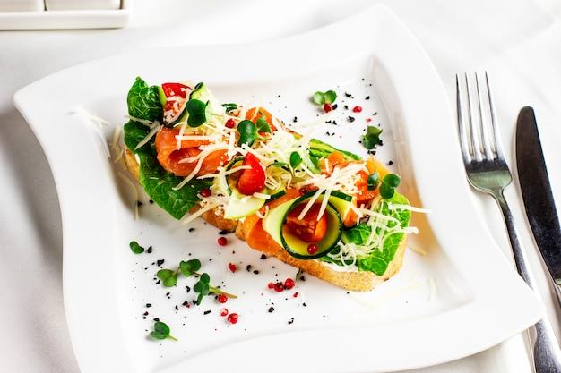 Bruschetta mit roten lachsfischen, frischgemüse und kräutern auf einer weißen platte