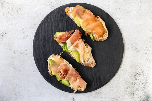 Bruschetta mit schinken und frischkäse und meecrogreens. brot mit geräuchertem speck und frischkäse.
