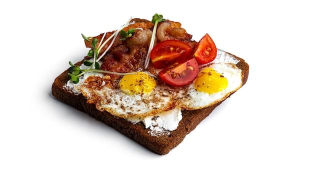 Bruschetta mit speck, eiern und gemüse auf weißem grund. hochwertiges foto