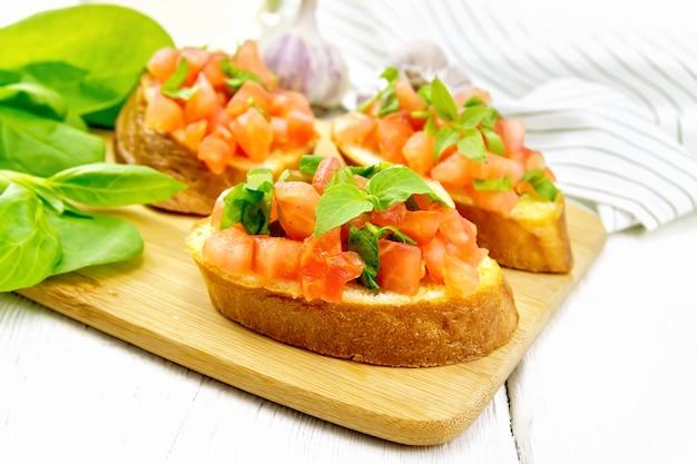 Bruschetta mit tomate, basilikum und spinat auf einem teller, frischen spinatblättern, serviette und pflanzenöl in einer karaffe auf holzbretthintergrund