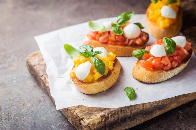 Bruschetta mit tomaten, basilikum und mozzarella-käse auf holzbrett. traditionelle italienische vorspeise oder snack, antipasto