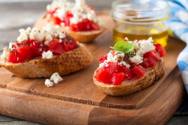 Bruschetta mit tomaten, feta und basilikum. traditioneller griechischer snack auf holzoberfläche. selektiver fokus.