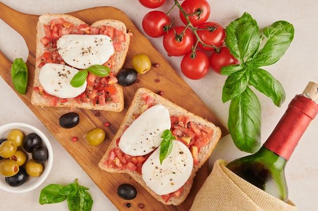 Bruschetta mit tomaten, mozzarella und basilikum auf einem schneidebrett. traditionelle italienische vorspeise oder snack, antipasti. caprese salat bruschetta. draufsicht mit kopierraum. flach liegen.
