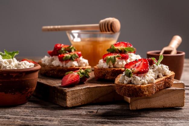 Bruschetta mit vollkornbrot, hüttenkäse ricotta, honig, chia, erdbeere, kopierraum. sommermenü catering