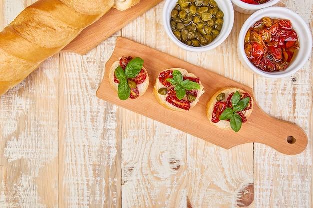 Bruschetta oder crostini mit sonnengetrockneten tomaten und kapern