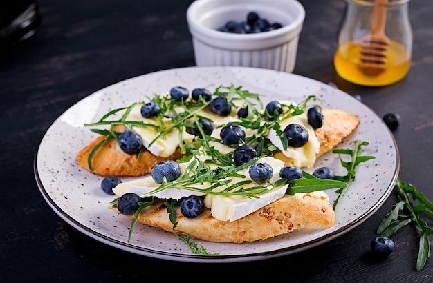 Bruschetta. toast crostini mit frischen beeren heidelbeere und honig, brie, rucola. italienische küche