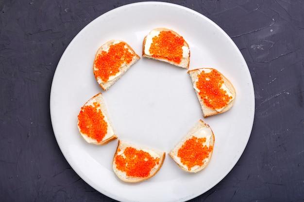 Bruschettes mit butter und rotem kaviar auf einem weißen teller, der schön auf einem grauen betonhintergrund-kopienraum ausgelegt ist. horizontales foto