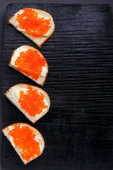 Bruschettes mit butter und rotem kaviar auf einer schwarzen tafel auf einer grauen betonoberfläche