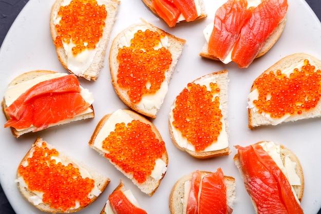 Bruschettes mit butter und rotem kaviar und lachs auf einem weißen teller. horizontales foto