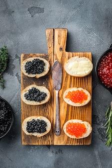 Bruschettes mit butterrot und schwarzem kaviar, auf grauem hintergrund, draufsicht flach