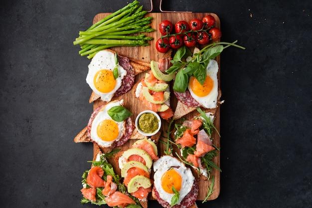 Brushetta oder sandwich auf dem brett über schwarzem beton gesetzt