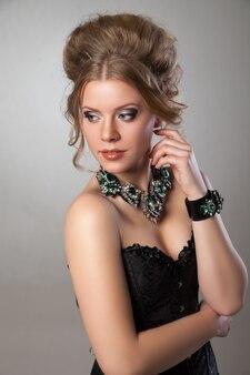 Brustbild einer schönen frau mit abend-make-up und großer halskette und armband. schmuck und schönheit. modefoto