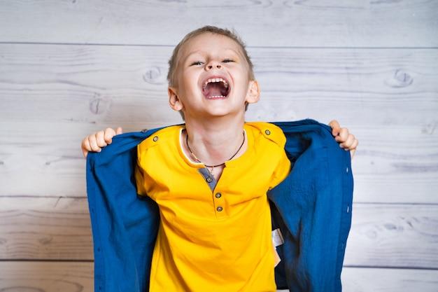 Brustbild eines frohen jungen, der sein blaues hemd beim schauen entfernt. glücklicher kleiner junge mit dem geöffneten mundlachen