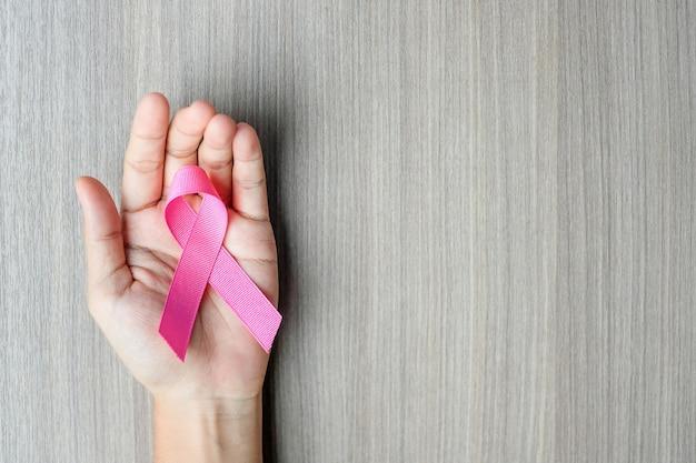 Brustkrebs-bewusstsein, frauenhand, die rosa band hält