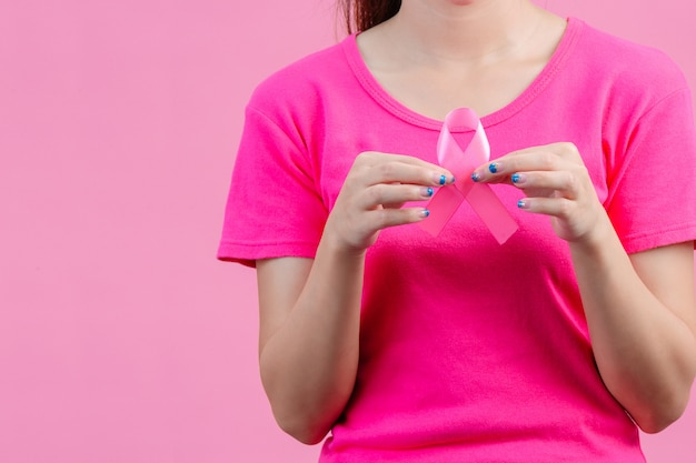 Brustkrebs-bewusstsein montn, frauen, die rosa hemden tragen ein rosa band mit beiden händen halten zeigen sie den symbolthe tag gegen brustkrebs