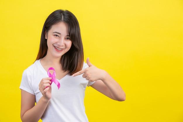 Brustkrebs, eine frau in einem weißen t-shirt mit einem satinrosa-band auf ihrer brust, ein symbol für brustkrebsbewusstsein