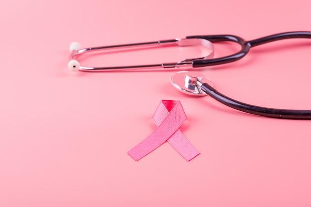Brustkrebsbewusstsein, pink ribbon mit stethoskop zur unterstützung von menschen, die leben und krank sind. frauengesundheits- und weltkrebstagkonzept