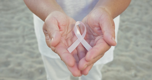 Brustkrebsbewusstseinsband in den händen der frau