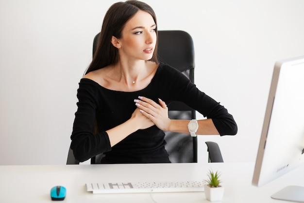 Brustschmerzen. frau, die panikattacke am arbeitsplatz hat