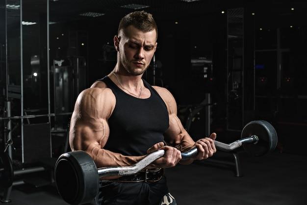 Brutal starke sportliche männer bodybuilder trainiert im fitnessstudio