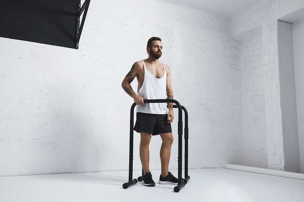Brutal tätowierter bärtiger männlicher athlet im leeren weißen panzer-t-shirt, das neben parallelstangen und zugstange steht, die auf seite schauen, bereit zum training, auf seite schauend