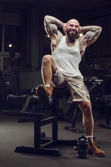 Brutal tätowierter bärtiger mann im fitnessstudio. fitness und bodybuilding. kaukasischer mann, der übungen im fitnessstudio macht.