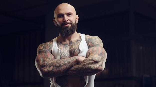 Brutal tätowierter bärtiger mann im fitnessstudio