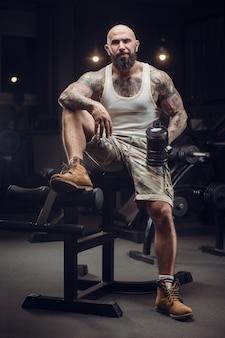 Brutal tätowierter bärtiger mann im trinkwasser der turnhalle nach dem training. fitness und bodybuilding. kaukasischer mann, der übungen im fitnessstudio macht.