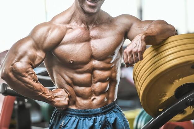 Brutale gealterte starke bodybuilder-sportler, die muskeln mit hanteln aufpumpen